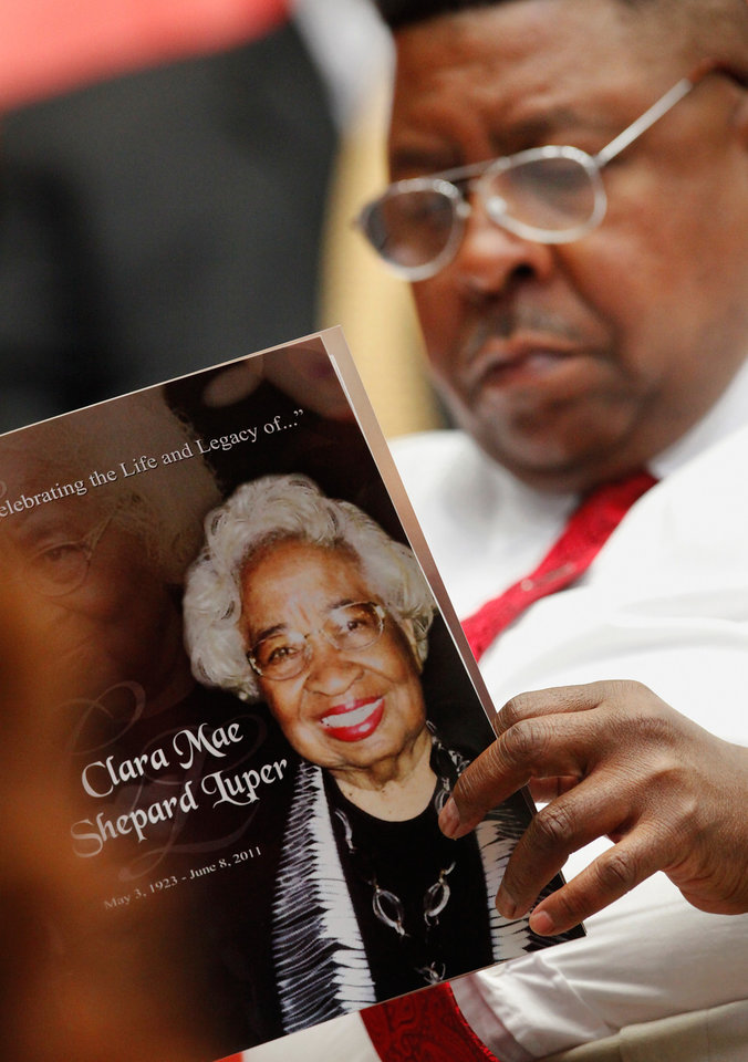 Photo - A man reads the program at the service. About 2,500 people celebrated the life and legacy of Oklahoma City civil rights pioneer Clara Mae Shepard Luper  during a lively service in the Cox Convention Center that lasted more than three hours, Friday,  June 17, 2011.  Luper died  last week at the age of 88. Photo by Jim Beckel, The Oklahoman