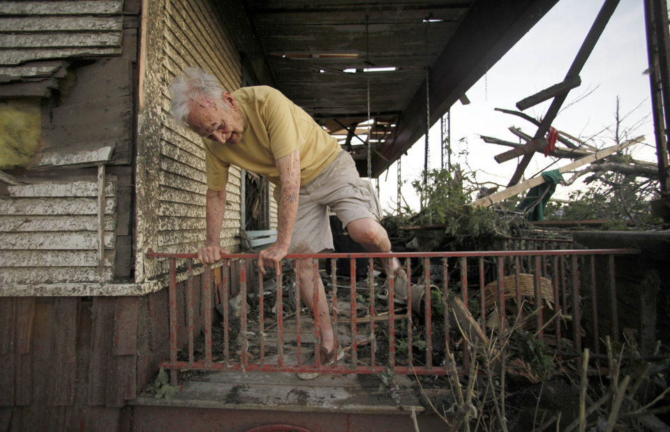 Photo - Don Atteberry, 89, crawls over a rail at his home that was severely damaged by a tornado in Joplin, Mo., Monday, May 23, 2011. A large tornado moved through much of the city Sunday, damaging a hospital and hundreds of homes and businesses and killing at least 89 people. (AP Photo/Charlie Riedel) ORG XMIT: MOCR206