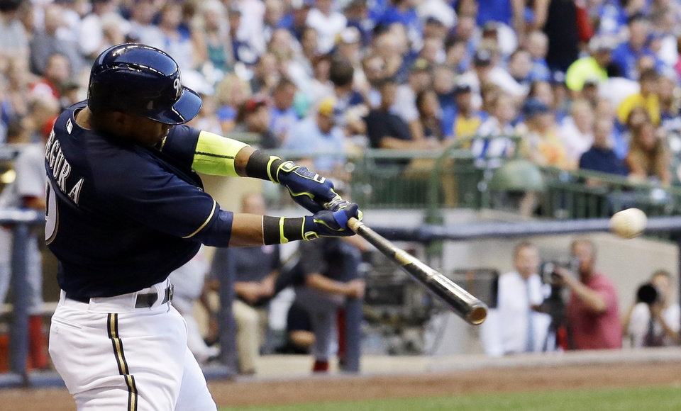 Photo - Milwaukee Brewers' Jean Segura hits a triple during the third inning of a baseball game against the Cincinnati Reds Monday, July 21, 2014, in Milwaukee. Segura scored on a throwing error. (AP Photo/Morry Gash)