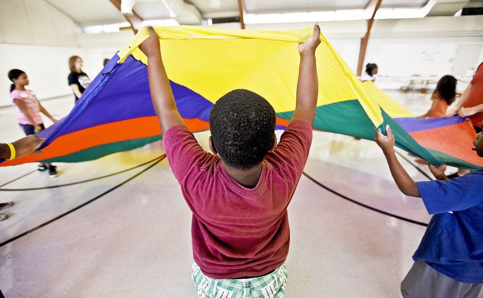 Photo - Leontre Titus works his arms to wave the parachute as campers play games Tuesday during the Kids Rock Camp at Britton Christian Church in Oklahoma City. Photos by Chris Landsberger, The Oklahoman
