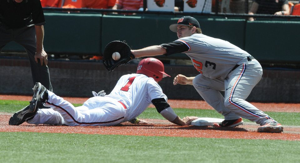 Photo - UNLVs Joey Swanner dives safely back into first base in front of Oregon State's Kavin Keyes during an NCAA college baseball regional tournament game in Corvallis, Ore., Sunday, June 1, 2014. (AP Photo/Mark Ylen)