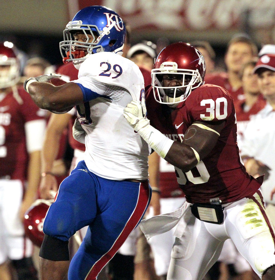 Oklahoma Sooner Javon Harris (30) pulls James Sims (29) out of bounds during the second half of the college football game where the University of Oklahoma Sooners (OU) defeated the University of Kansas Jayhawks (KU) 52-7 at Gaylord Family-Oklahoma Memorial Stadium in Norman, Okla., on Saturday, Oct. 20, 2012. Photo by Steve Sisney, The Oklahoman