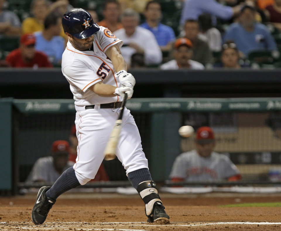 Photo - Houston Astros' Jose Altuve hits a double against the Cincinnati Reds in the first inning of a baseball game Wednesday, Sept. 18, 2013, in Houston. (AP Photo/Pat Sullivan)