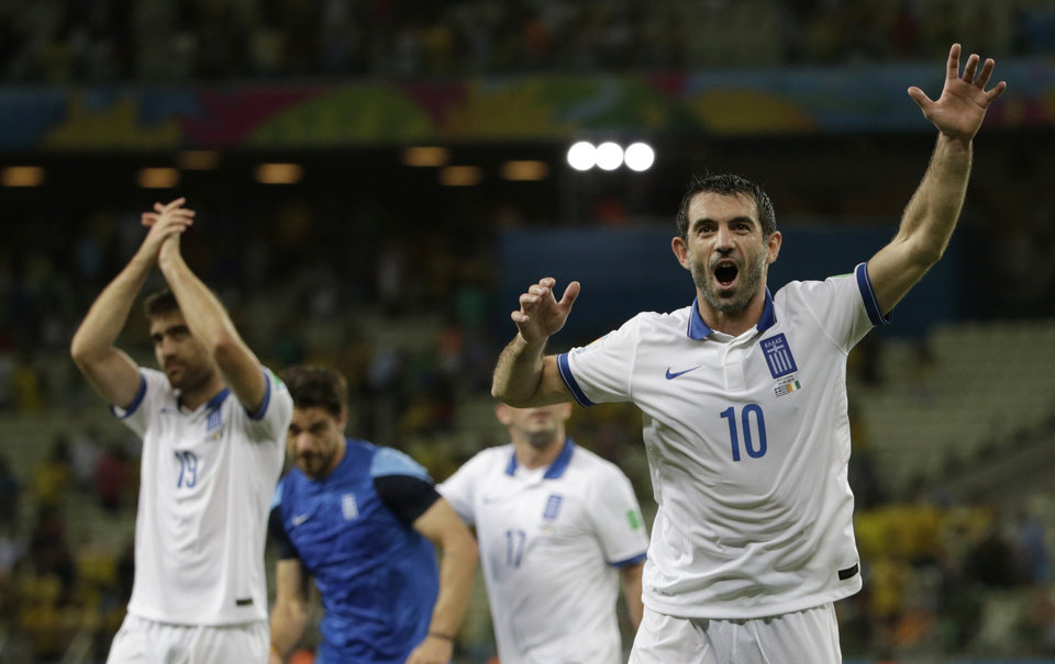 Photo - Greece's Giorgos Karagounis, right, waves to supporters as he celebrates his side's 2-1 win after the group C World Cup soccer match between Greece and Ivory Coast at the Arena Castelao in Fortaleza, Brazil, Tuesday, June 24, 2014. (AP Photo/Fernando Llano)