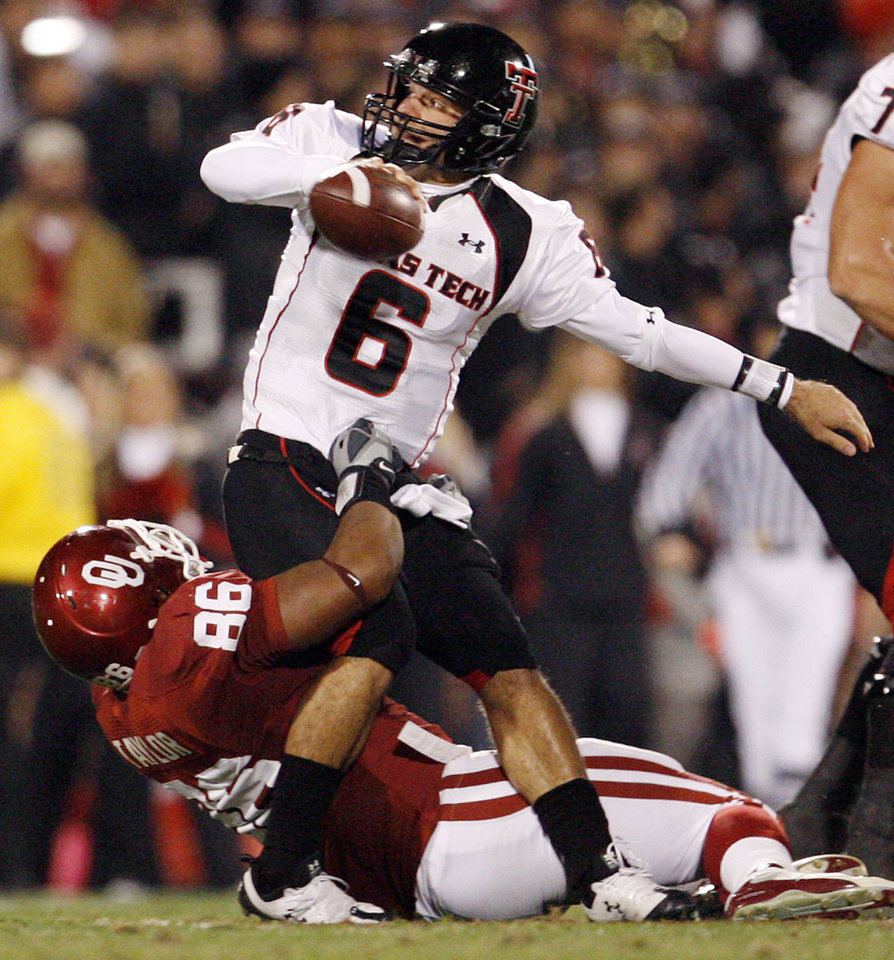 Texas Tech quarterback Graham Harrell tries to get rid of the ball as he is brought down by OU's Adrian Taylor (86) in the first quarter of the college football game between the University of Oklahoma Sooners and Texas Tech University at Gaylord Family -- Oklahoma Memorial Stadium in Norman, Okla., Saturday, Nov. 22, 2008. BY NATE BILLINGS, THE OKLAHOMAN