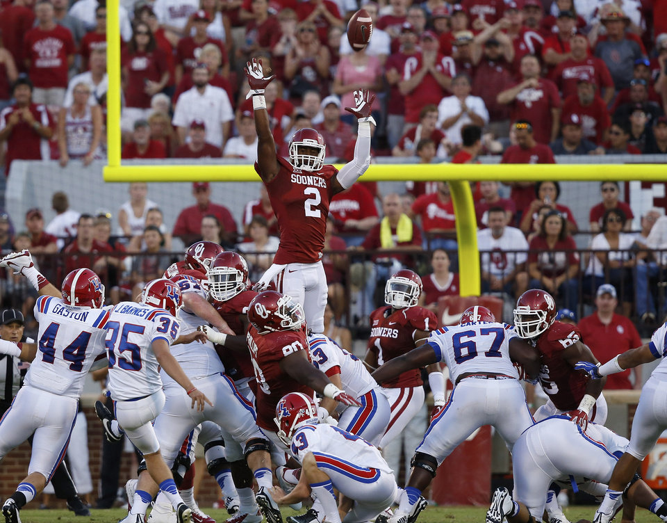 Photo - Louisiana Tech's Jonathan Barnes (35) kicks a field goal over Oklahoma's Julian Wilson (2) and the rest of the Oklahoma team in the second quarter of an NCAA college football game in Norman, Okla., Saturday, Aug. 30, 2014. (AP Photo/Sue Ogrocki)