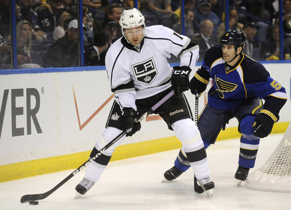 Photo - Los Angeles Kings' Justin Williams (14) looks to pass in front of St. Louis Blues' Barret Jackman (5) during the first period of Game 1 of their first-round NHL hockey Stanley Cup playoff series, Tuesday, April 30, 2013, in St. Louis. (AP Photo/Bill Boyce)