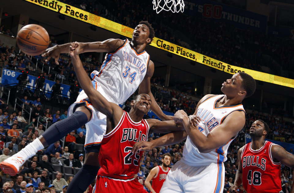 Photo - Oklahoma City's Hasheem Thabeet (34) and Daniel Orton (33) fight for a rebound with Chicago's Marquis Teague (25) and Nazr Mohammed (48) during the NBA game between the Oklahoma City Thunder and the Chicago Bulls at Chesapeake Energy Arena in Oklahoma City, Sunday, Feb. 24, 2013. Photo by Sarah Phipps, The Oklahoman