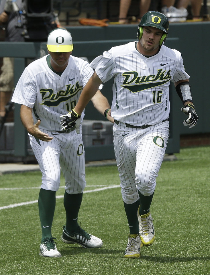 Photo - Oregon catcher Shaun Chase (16) is congratulated by third base coach Jay Uhlman (10) after Chase hit a three-run home run against Clemson during the fourth inning of an NCAA college baseball regional tournament game Friday, May 30, 2014, in Nashville, Tenn. (AP Photo/Mark Humphrey)