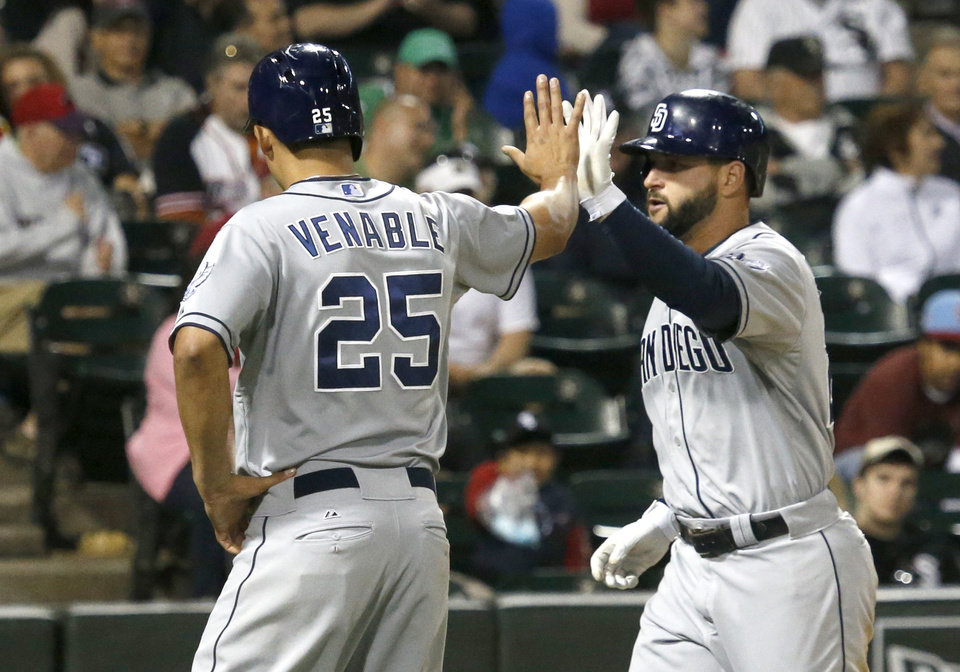 Photo - San Diego Padres' Will Venable (25) greets Yonder Alonso at home after they both scored on Alonso's home run off Chicago White Sox relief pitcher Javy Guerra during the eighth inning of an interleague baseball game Friday, May 30, 2014, in Chicago. (AP Photo/Charles Rex Arbogast)
