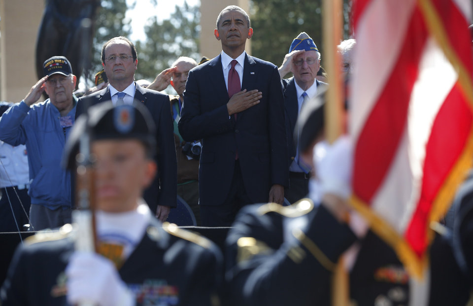 Photo - U.S. President Barack Obama, centre and French President Francois Hollande stand, during the playing of the Star Spangled Banner, at Normandy American Cemetery at Omaha Beach as he participates in the 70th anniversary of D-Day in Colleville sur Mer, in Normandy, France, Friday, June 6, 2014. (AP Photo/Charles Dharapak)