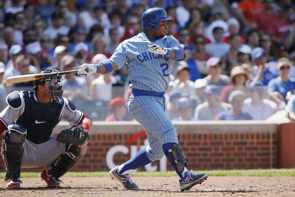 Photo - Chicago Cubs' Luis Valbuena, right, hits a single against the St. Louis Cardinals during the seventh inning of a baseball game on Sunday, July 27, 2014, in Chicago. (AP Photo/Andrew A. Nelles)