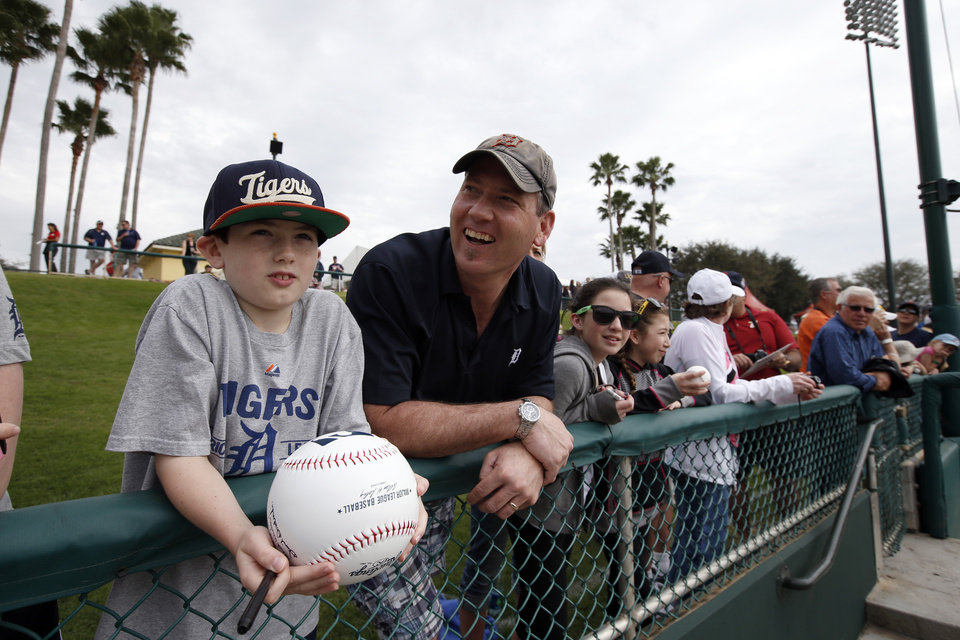 Photo - Gideon Kowalczyk, 10, and his father, John Kowalczyk, both from Bay City, Mich., wait for autographs before a spring exhibition baseball game between the Detroit Tigers and the Atlanta Braves, Wednesday, Feb. 26, 2014, in Kissimmee, Fla. After such a long, cold season, Americans across the winter-weary Midwest and the East Coast are desperate to escape to warm-weather destinations in California, Arizona and Florida. (AP Photo/Alex Brandon)