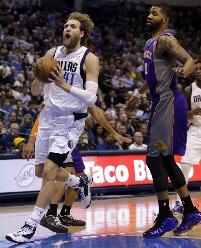 Photo - Dallas Mavericks forward Dirk Nowitzki (41), of Germany, drives past Phoenix Suns forward Markieff Morris (11) during the first half of an NBA basketball game, Wednesday, April 10, 2013, in Dallas. (AP Photo/LM Otero)