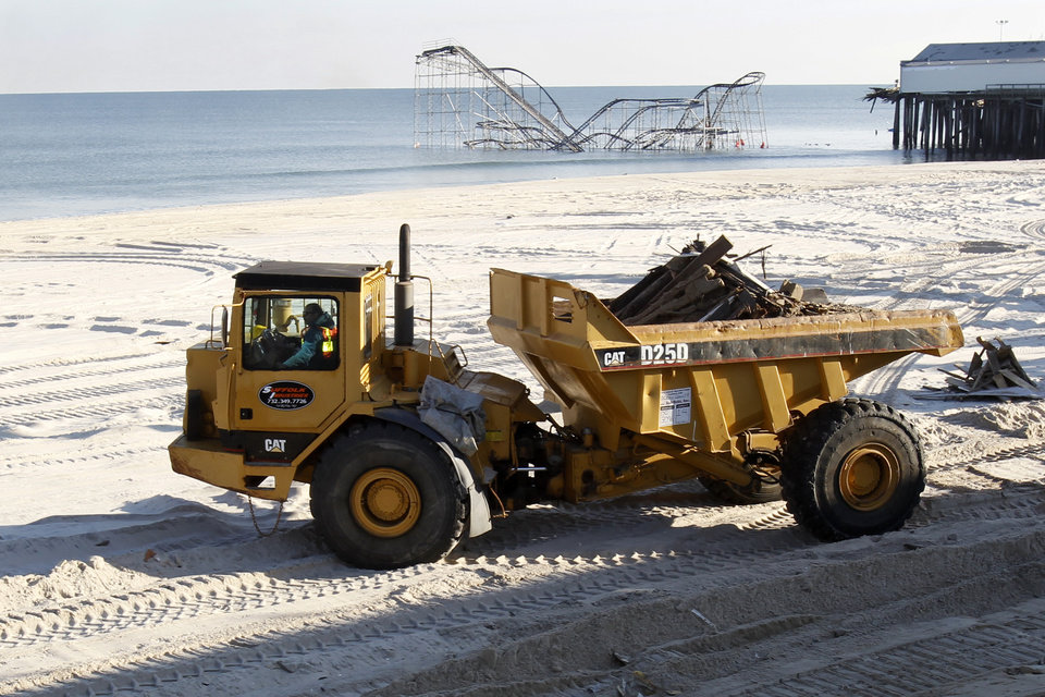 Photo - A large construction vehicle carries remnants of the boardwalk in Seaside Heights, N.J., Thursday, Jan. 3, 2013, that was destroyed two months ago by Superstorm Sandy. Under intense pressure from angry Republicans, House Speaker John Boehner has agreed to a vote this week on aid for Superstorm Sandy recovery.   (AP Photo/Mel Evans)