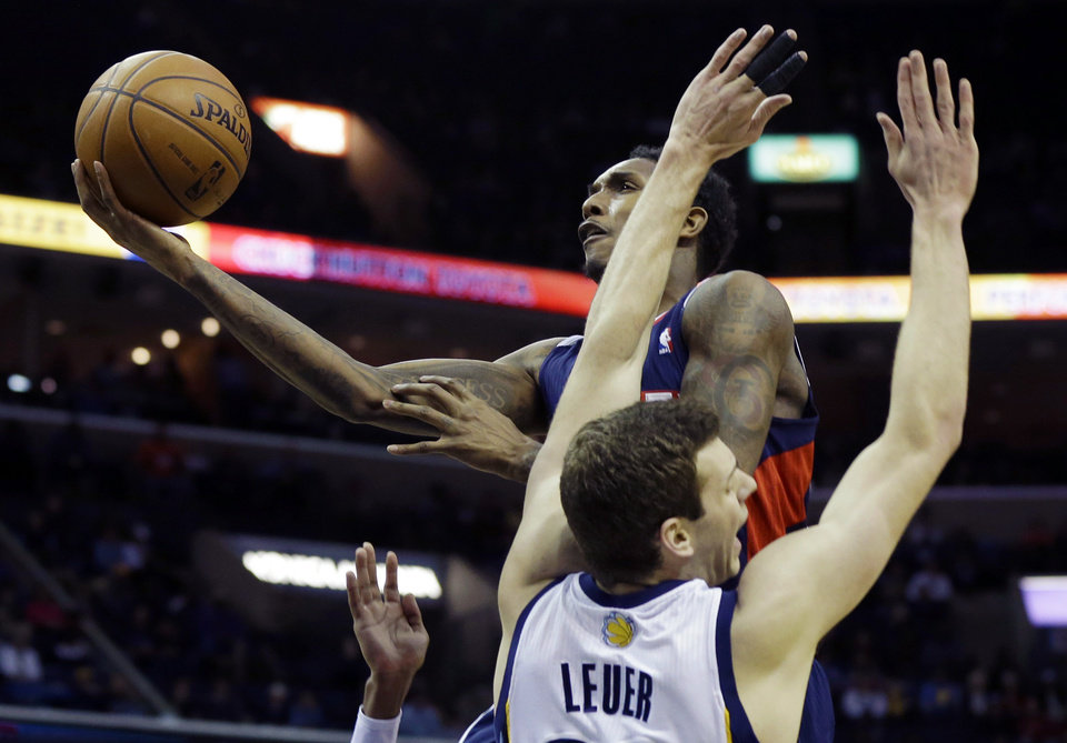 Photo - Atlanta Hawks' Louis Williams goes to the basket over Memphis Grizzlies' Jon Leuer in the first half of an NBA basketball game in Memphis, Tenn., Sunday, Jan. 12, 2014. (AP Photo/Danny Johnston)