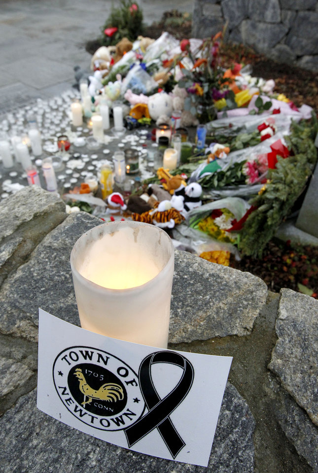 Photo - A note rests next to a candle near a makeshift memorial outside of St. Rose of Lima Roman Catholic Church following a Sunday Mass, Sunday, Dec. 16, 2012, in Newtown, Conn. On Friday, a gunman allegedly killed his mother at their home and then opened fire inside the Sandy Hook Elementary School in Newtown, killing 26 people, including 20 children. (AP Photo/Julio Cortez)