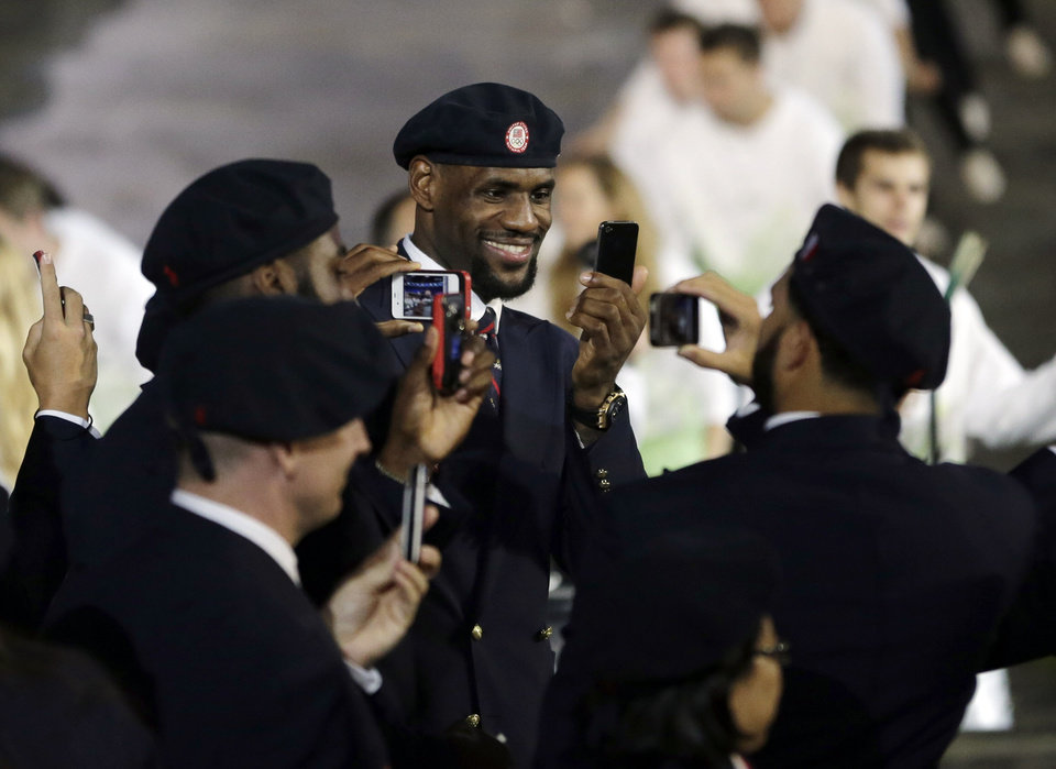 Professional basketball player LeBron James takes pictures with members of the the United States' Olympic team during the Opening Ceremony at the 2012 Summer Olympics, Friday, July 27, 2012, in London.  (AP Photo/Matt Slocum) ORG XMIT: OLYOC536