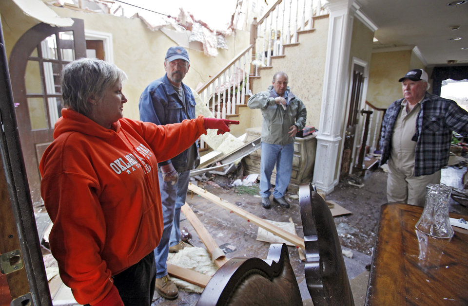 Photo - Tammy Blankenship talks to her family about what to remove from her home that was heavily damaged in the Oak Tree addition on Wednesday, Feb. 11, 2009, after a tornado hit the area on Tuesday in Edmond, Okla.  PHOTO BY CHRIS LANDSBERGER, THE OKLAHOMAN