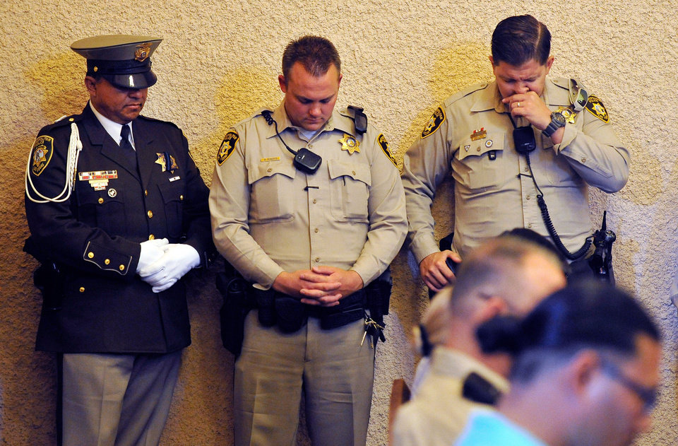 Photo - Las Vegas police bow their heads during a memorial service for Joseph Wilcox at Palm Downtown Mortuary on Sunday, June 22, 2014, in Las Vegas. Wilcox went for his own legal and concealed handgun after a couple killed Officers Igor Soldo and Alyn Beck at a nearby pizza shop and walked into a Wal-Mart, fired a shot in the air, and declared the start of a revolution two weeks ago. (AP Photo/Las Vegas Review-Journal, David Becker, Pool)