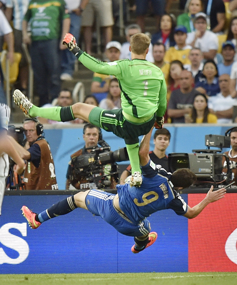 Photo - Germany's goalkeeper Manuel Neuer, top, clatters into Argentina's Gonzalo Higuain during the World Cup final soccer match between Germany and Argentina at the Maracana Stadium in Rio de Janeiro, Brazil, Sunday, July 13, 2014. (AP Photo/Martin Meissner)