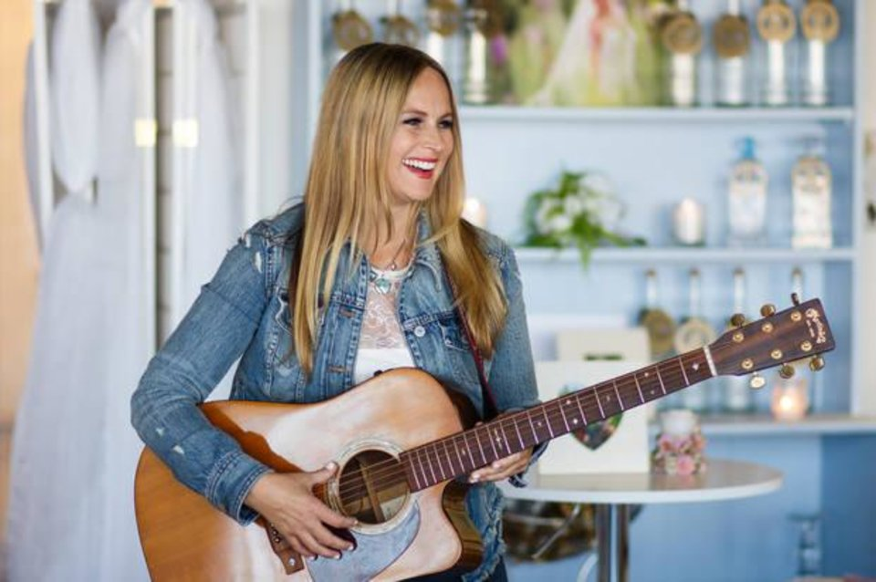Photo -  Leigh Madison holds her guitar before performing a private concert June 28 at the Ever Ever Studio in Oklahoma City. Madison, who found success on Broadway, is shifting her focus to writing and performing country music. [Photo by Anya Magnuson, The Oklahoman]