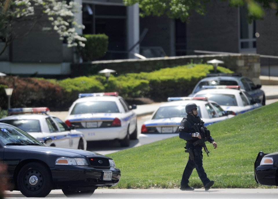 Photo - A police officer walks near WMAR-TV, after a truck driven by a man rammed the Baltimore-area television station Tuesday, May 13, 2014 leaving a gaping hole in the front of the building, in Towson, Md. Police were still searching for the driver. They said they didn't know of a motive and didn't find weapons in the truck, but they assumed the driver may be dangerous because he ran into the occupied building.  The station believes everyone inside evacuated safely, News Director Kelly Groft said. (AP Photo/Steve Ruark)