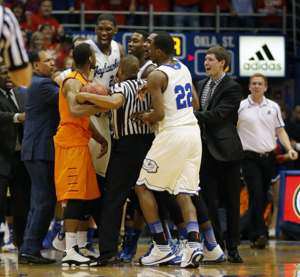 Photo - Referee Keith Kimble, center, gets between Oklahoma State guard Markel Brown (22) and Kansas center Joel Embiid (21), forward Jamari Traylor (31) and guard Andrew Wiggins (22) during the first half of an NCAA college basketball game at Allen Fieldhouse in Lawrence, Kan., Saturday, Jan. 18, 2014. (AP Photo/Orlin Wagner)