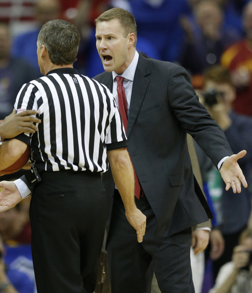 Photo - Iowa State head coach Fred Hoiberg, right, pleads his case after being called for a technical foul during the first half of an NCAA college basketball game against Kansas in the semifinals of the Big 12 Conference men's tournament in Kansas City, Mo., Friday, March 14, 2014. (AP Photo/Orlin Wagner)