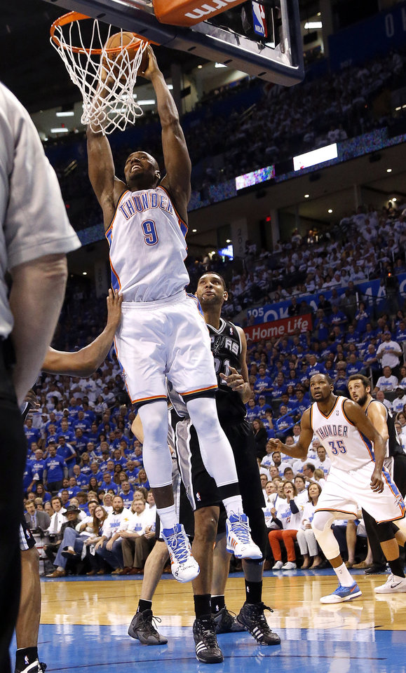 Photo - Oklahoma City's Serge Ibaka (9) dunks in front of San Antonio's Tim Duncan (21) during Game 4 of the Western Conference Finals in the NBA playoffs between the Oklahoma City Thunder and the San Antonio Spurs at Chesapeake Energy Arena in Oklahoma City, Tuesday, May 27, 2014. Photo by Nate Billings, The Oklahoman