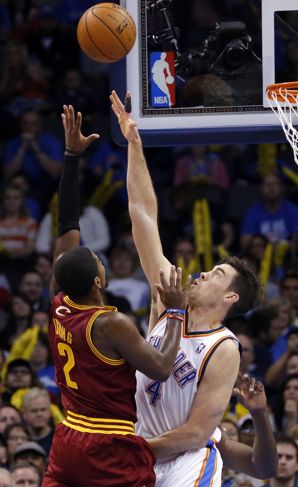 Photo - Oklahoma City's Nick Collison (4) defends agains Cleveland's Kyrie Irving (2) during the NBA basketball game between the Oklahoma City Thunder and the Cleveland Cavaliers at the Chesapeake Energy Arena, Sunday, Nov. 11, 2012. Photo by Sarah Phipps, The Oklahoman