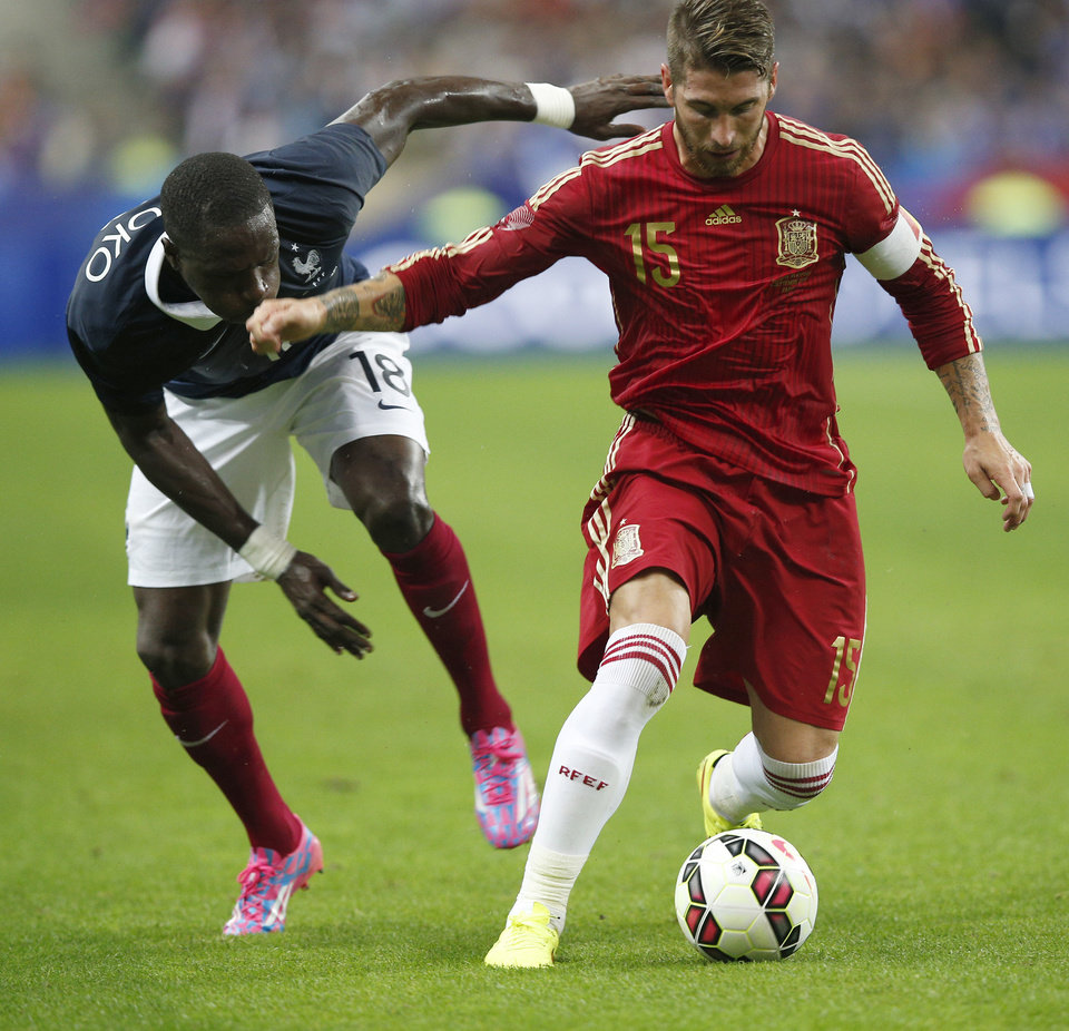 Photo - France's Moussa Sissoko, left, and Spain's Sergio Ramos battles for the ball during their international friendly soccer match at the Stade de France in Saint Denis, outside Paris, Thursday, Sept. 4, 2014. (AP Photo/Christophe Ena)