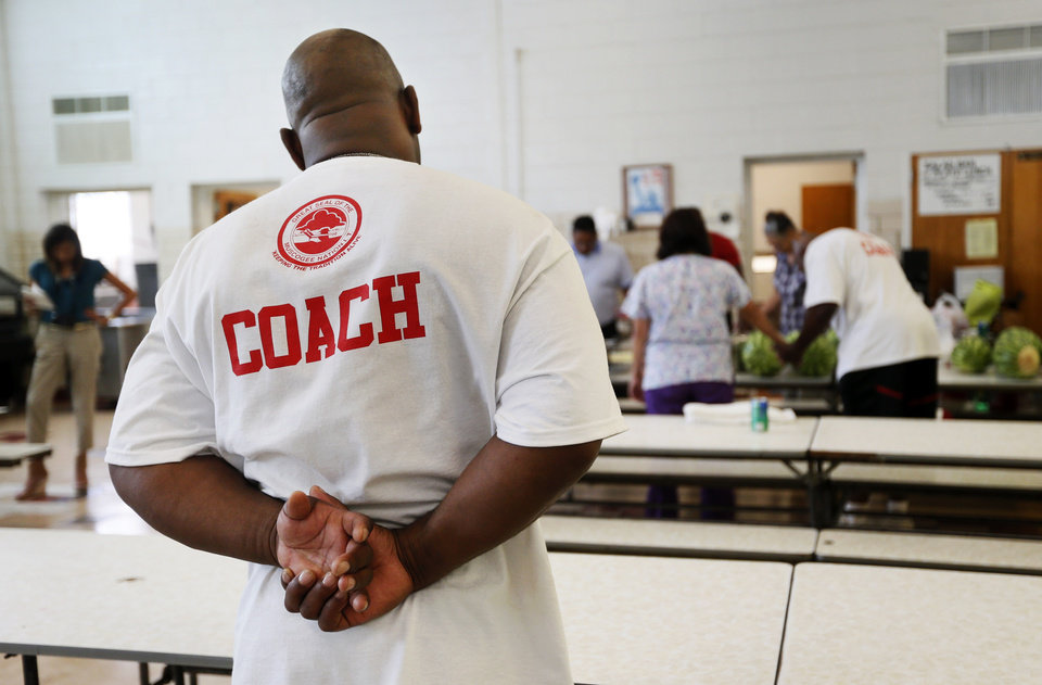 Photo - Former OU quarterback Jamelle Holieway leads the prayer before a barbecue dinner for staff and volunteers at Holieway's Spirit of Oklahoma football camp in Weleetka, Okla., Friday, July 6, 2012. Photo by Nate Billings, The Oklahoman