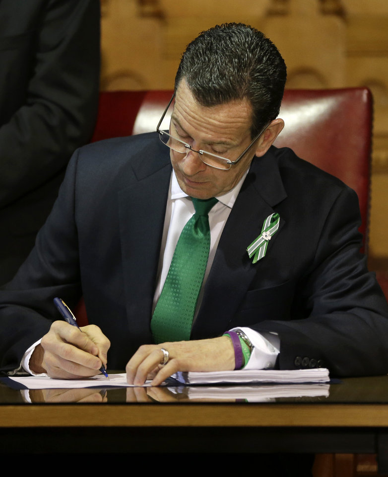 Photo - Connecticut Gov. Dannel P. Malloy signs legislation at the Capitol in Hartford, Conn., Thursday, April 4, 2013, which includes new restrictions on weapons and large capacity ammunition magazines, a response to last year's deadly school shooting in Newtown. The legislation adds more than 100 firearms to the state's assault weapons ban, sets eligibility rules for buying ammunition, and creates what officials have called the nation's first dangerous weapon offender registry. Some parts of the bill would take effect immediately after Malloy's signature, including background checks for all firearms sales. (AP Photo/Steven Senne)