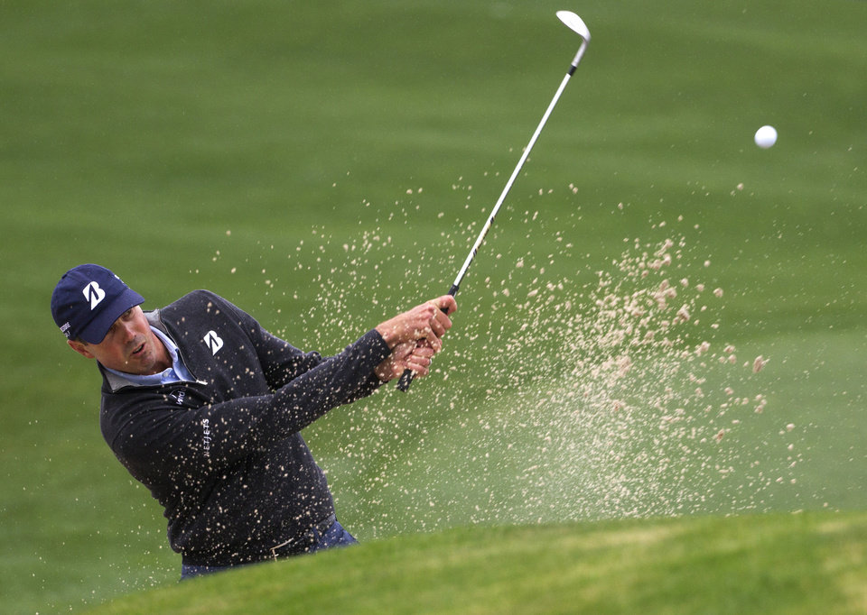 Photo - Matt Kuchar takes shot out of the bunker on the 18th green during a playoff hole against Matt Jones in the final round of the Houston Open golf tournament, Sunday, April 6, 2014, in Humble, Texas. Matt Jones won the playoff to become the Houston Open champion. (AP Photo/Patric Schneider)