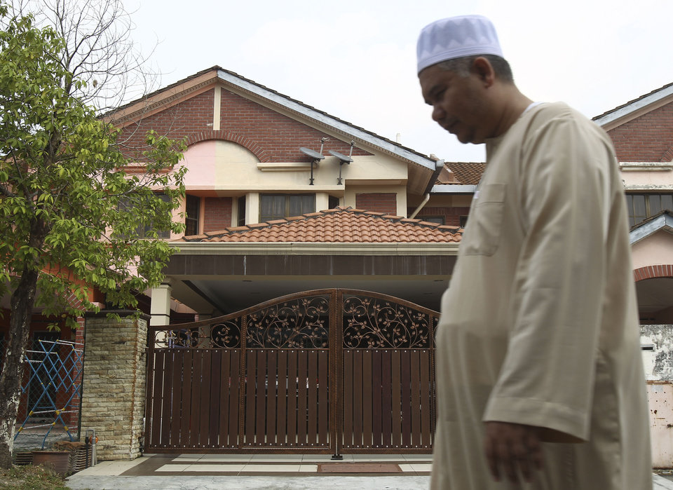 Photo - A Muslim man walks past the missing Malaysia Airlines co-pilot Fariq Abdul Hamid's house after a prayer in Shah Alam, outside Kuala Lumpur, Malaysia, Saturday, March 15, 2014. Malaysian police have already said they are looking at the psychological state, the family life and connections of pilot Zaharie, 53, and co-pilot Fariq Abdul Hamid, 27. Both have been described as respectable, community-minded men. The Malaysian jetliner missing for more than a week had its communications deliberately disabled and its last signal came about 7 1/2 hours after takeoff, meaning it could have ended up as far as Kazakhstan or into the southern reaches of the Indian Ocean, Malaysian Prime Minister Najib Razak said Saturday. (AP Photo/Lai Seng Sin)
