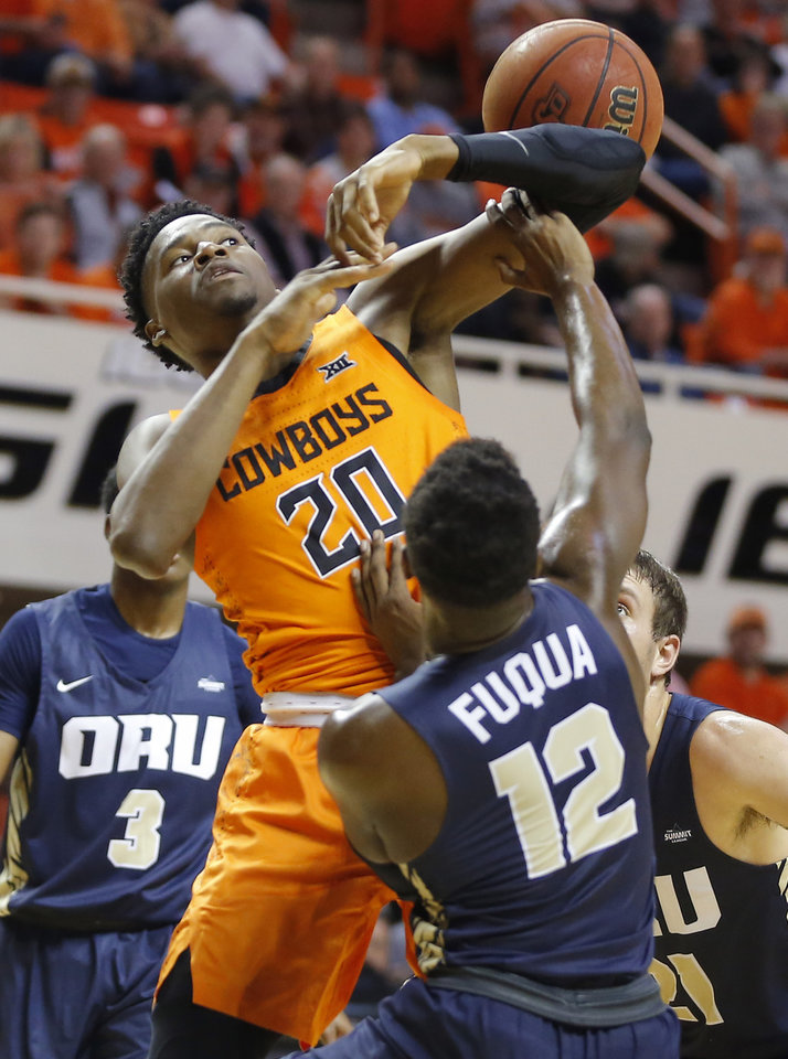 Photo - Oklahoma State's Keylan Boone (20) is fouled as he lose the ball in front of Oral Roberts' R.J. Fuqua (12) during an NCAA basketball game between the Oklahoma State University Cowboys (OSU) and the Oral Roberts Golden Eagles (ORU) at Gallagher-Iba Arena in Stillwater, Okla., Wednesday, Nov. 6, 2019. [Bryan Terry/The Oklahoman]