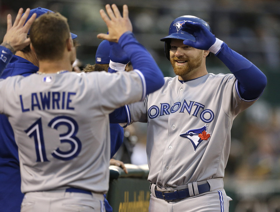 Photo - Toronto Blue Jays' Adam Lind, right, is congratulated by Brett Lawrie (13) after Lind hit a home run off Oakland Athletics' A.J. Griffin in the fifth inning of a baseball game Monday, July 29, 2013, in Oakland, Calif. (AP Photo/Ben Margot)