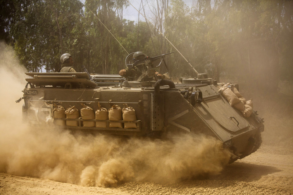 Photo - An Israeli armored personnel carrier moves near the Israel and Gaza border, Saturday, July 19, 2014. Israel pounded Hamas rocket launchers, uncovered more than a dozen cross-border tunnels and engaged in gunbattles with Palestinian militants Saturday, as fighting intensified on the second day of its open-ended ground operation in Gaza, as the Palestinian death toll continued to rise. (AP Photo/Dusan Vranic)
