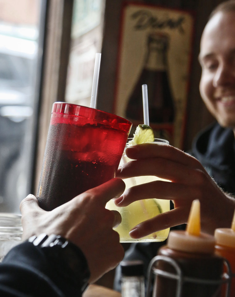 Photo - FILE - In this March 8, 2013 file photo, customers at Brother Jimmy's BBQ call cheers with 24-ounce, left, and 16-ounce beverages, in New York.  New York City's groundbreaking limit on the size of sugar-laden drinks has been struck down by a judge shortly before it was set to take effect. The restriction was supposed to start Tuesday, March 12, 2013. The rule prohibits selling non-diet soda and some other sugary beverages in containers bigger than 16 ounces. It applies at places ranging from pizzerias to sports stadiums, though not at supermarkets or convenience stores. (AP Photo/Bebeto Matthews)