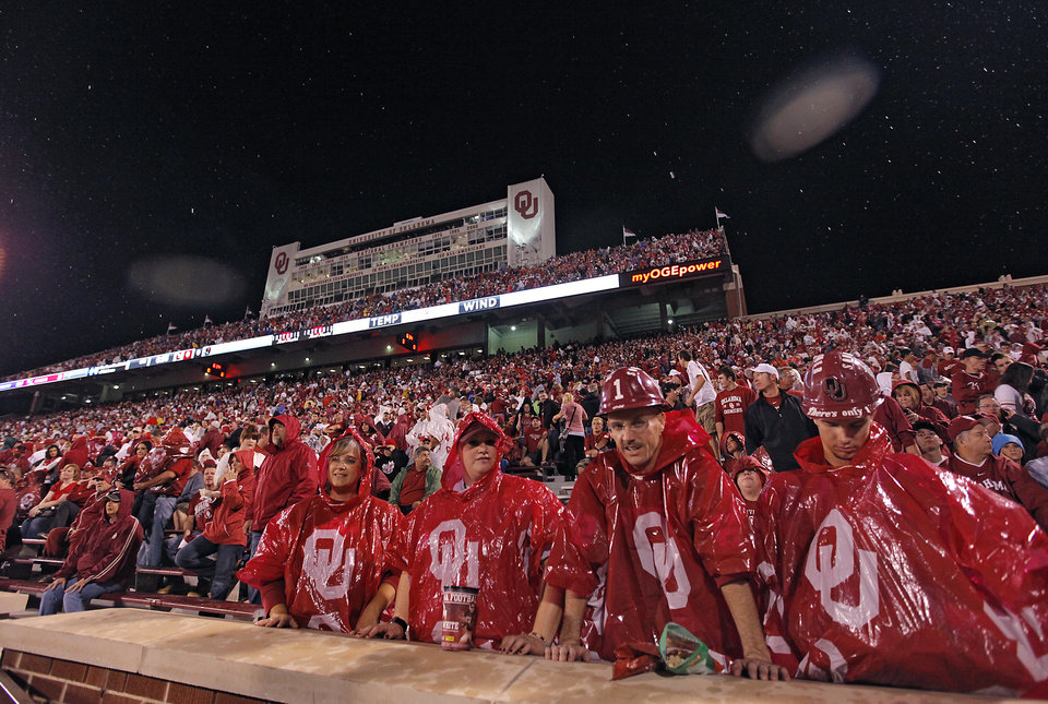 Photo - Sooner fans brave the storm delay in the stands before the start of the college football game between the University of Oklahoma Sooners (OU) and Texas Tech University Red Raiders (TTU) at the Gaylord Family-Oklahoma Memorial Stadium on Saturday, Oct. 22, 2011. in Norman, Okla. Photo by Chris Landsberger, The Oklahoman
