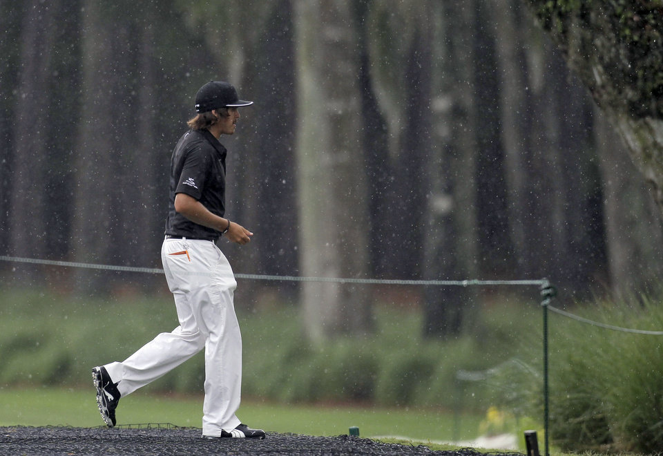 Rickie Fowler runs to a waiting van to avoid a heavy rain storm during a practice round for The Players Championship golf tournament Tuesday, May 8, 2012, at Sawgrass in Ponte Vedra Beach, Fla. (AP Photo/Chris O'Meara)