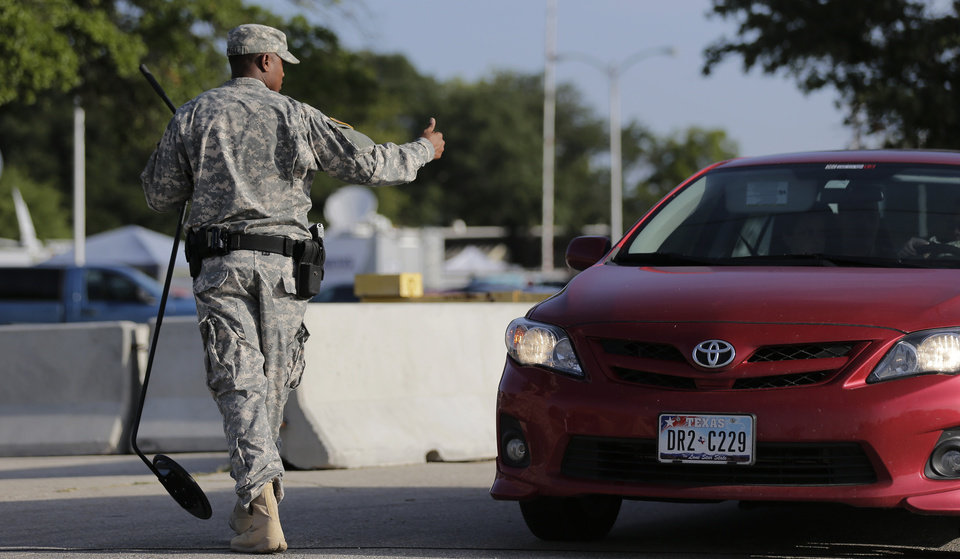 Photo - A driver gets the thumbs up at a security checkpoint to enter the Lawrence William Judicial Center as the sentencing phase for Maj. Nidal Hasan continues, Wednesday, Aug. 28, 2013, in Fort Hood, Texas. Hasan was found unanimously guilty on the 13 charges of premeditated murder and is eligible for the death penalty. (AP Photo/Eric Gay)
