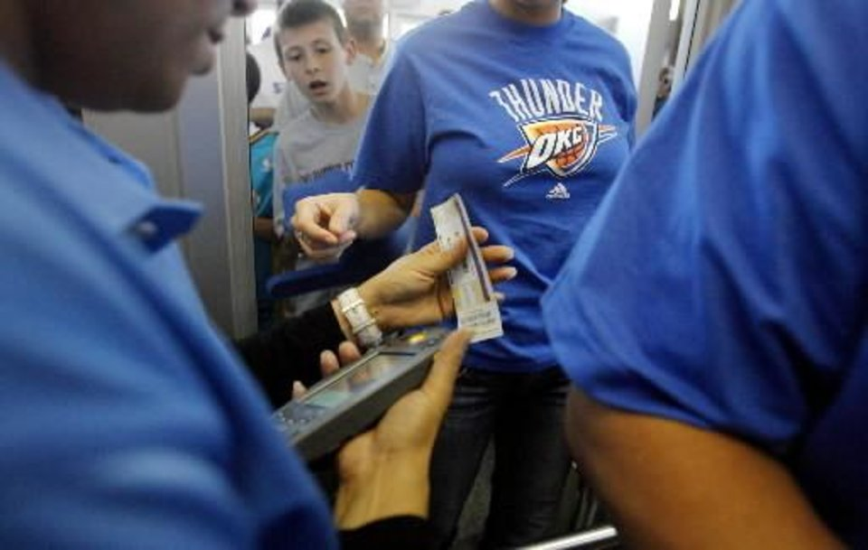 Photo -  Thunder fans have their  tickets scanned as the doors open for the opening night NBA basketball game between the Oklahoma City  Thunder and the Milwaukee Bucks on Wednesday, Oct. 29, 2008, at the Ford Center in Oklahoma City, Okla. BY CHRIS LANDSBERGER