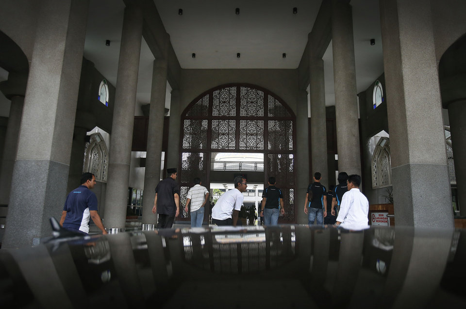 Photo - Muslim men arrive at the Kuala Lumpur International Airport Mosque for afternoon prayers where a special prayer session will be offered for the missing Malaysia Airlines flight MH370, Friday, March 14, 2014 in Sepang, Malaysia. Vietnam says it has downgraded but not stopped its search for the missing jetliner in the South China Sea and has been asked by Malaysian authorities to consider sending planes and ships to the Strait of Malacca. The statement Friday is a sign that the focus of the search effort is switching to the west of Malaysia, to the strait and further west into the Indian Ocean. (AP Photo/Wong Maye-E)