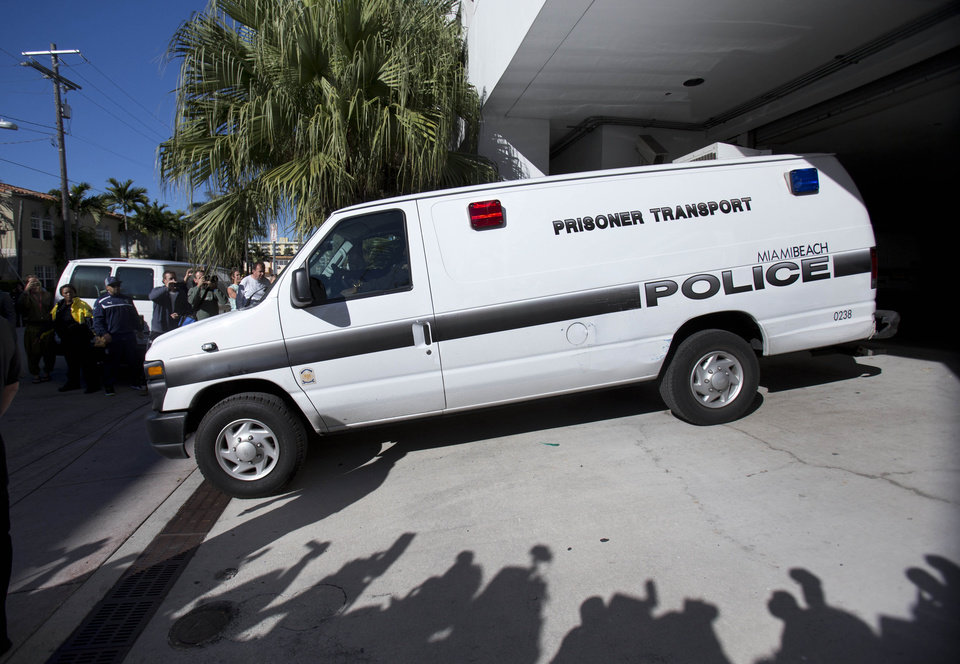 Photo - A Miami Beach, Fla., police prisoner transport van leaves the Miami Beach Police building believed to be transporting pop singer Justin Bieber and R&B singer known as Khalil after their arrest, Thursday, Jan. 23, 2014 in Miami Beach.   Bieber and Khalil both face drag-racing and driving under the influence charges. (AP Photo/Wilfredo Lee)
