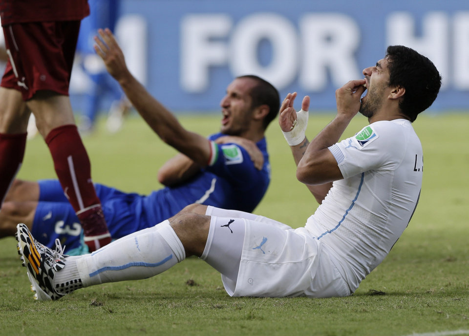 Photo - Uruguay's Luis Suarez holds his teeth after running into Italy's Giorgio Chiellini's shoulder during the group D World Cup soccer match between Italy and Uruguay at the Arena das Dunas in Natal, Brazil, Tuesday, June 24, 2014. (AP Photo/Ricardo Mazalan)