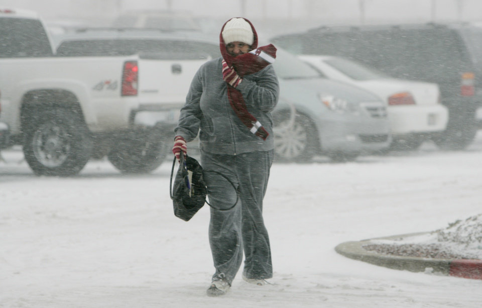Jennifer Shaw of Norman walks through blowing snow to do some last-minute shopping in Norman Thurs. Dec. 24, 2009. Photo by Jaconna Aguirre, The Oklahoman.