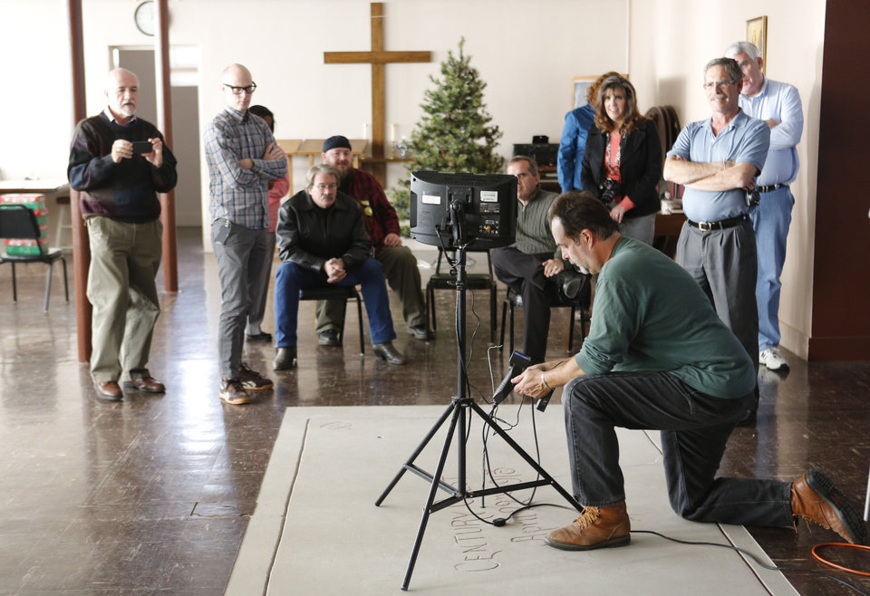 Photo - As several people look on, videographer Andy Slaucitajs uses an endoscope camera Wednesday to look inside a vault-like structure containing a time capsule at First Lutheran Church of Oklahoma City, 1300 N Robinson. PHOTO BY STEVE GOOCH, THE OKLAHOMAN