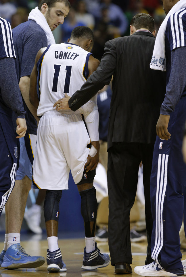 Photo - Memphis' Mike Conley (11) is helped off the court after an injury during Game 6  in the first round of the NBA playoffs between the Oklahoma City Thunder and the Memphis Grizzlies at FedExForum in Memphis, Tenn., Thursday, May 1, 2014. Oklahoma City won 104-84. Photo by Bryan Terry, The Oklahoman
